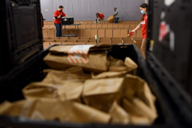 The Meadowlands YMCA gives out boxes of free food every Tuesday. Cars begin to line up hours before the food is handed out. Volunteers pack boxes in East Rutherford on Tuesday December 1, 2020.