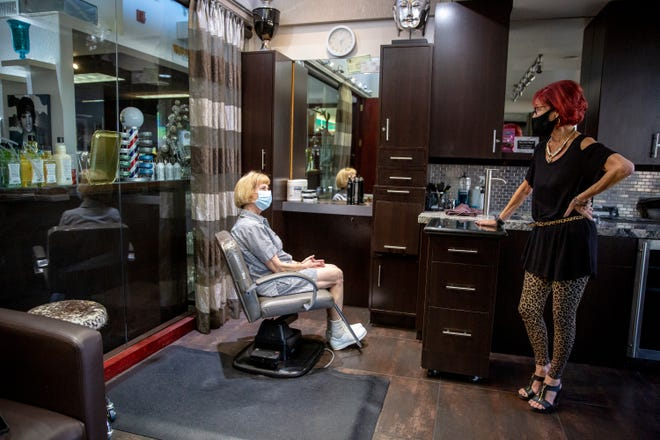 Meg Firestone, right, one of the owners of J. Russell! The Salon, and longtime customer Marilyn Gitt talk about the closure of the salon in Palm Desert, Calif., on Tuesday, December 1, 2020. The owners have announced that they will be closing the business at the end of the month.