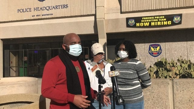 Community activist the Rev. Jarrett Maupin, Krystofer Lee and Iesha Stanciel address the news media during a press conference in front of Phoenix police headquarters in downtown Phoenix on Dec. 1, 2020.