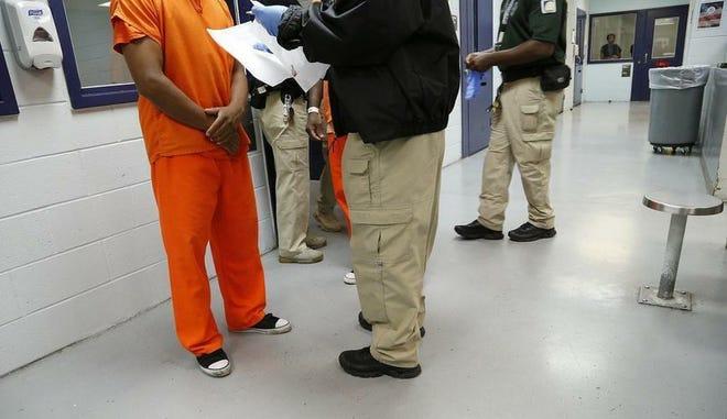En esta imagen del 24 de septiembre de 2015 se ve un detenido en uniforme naranja siendo procesado por un guardia dentro del Centro de Detención Krome, en Miami.