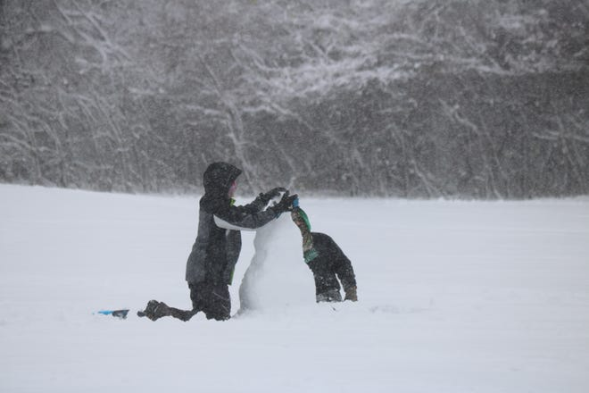 A couple of local children build a snowman at Portage Park in Port Clinton following the first major snowfall of the season on Tuesday morning.