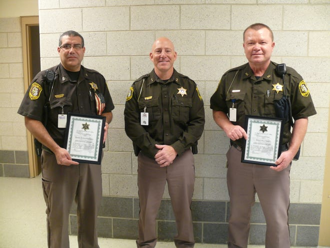 St. Clair County Sheriff corrections deputies Richard Rodriguez (left) and Kent Porter (right) receive life-saving awards from Sheriff Mat King on Tuesday, Dec. 1, 2020.