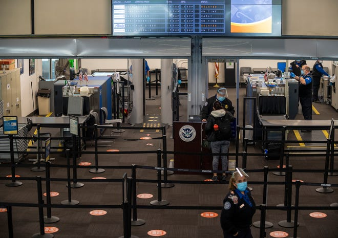A person prepares to go through the Transportation Security Administration line inside the Monterey Regional Airport in Monterey, Calif., on Tuesday, Dec. 1, 2020.
