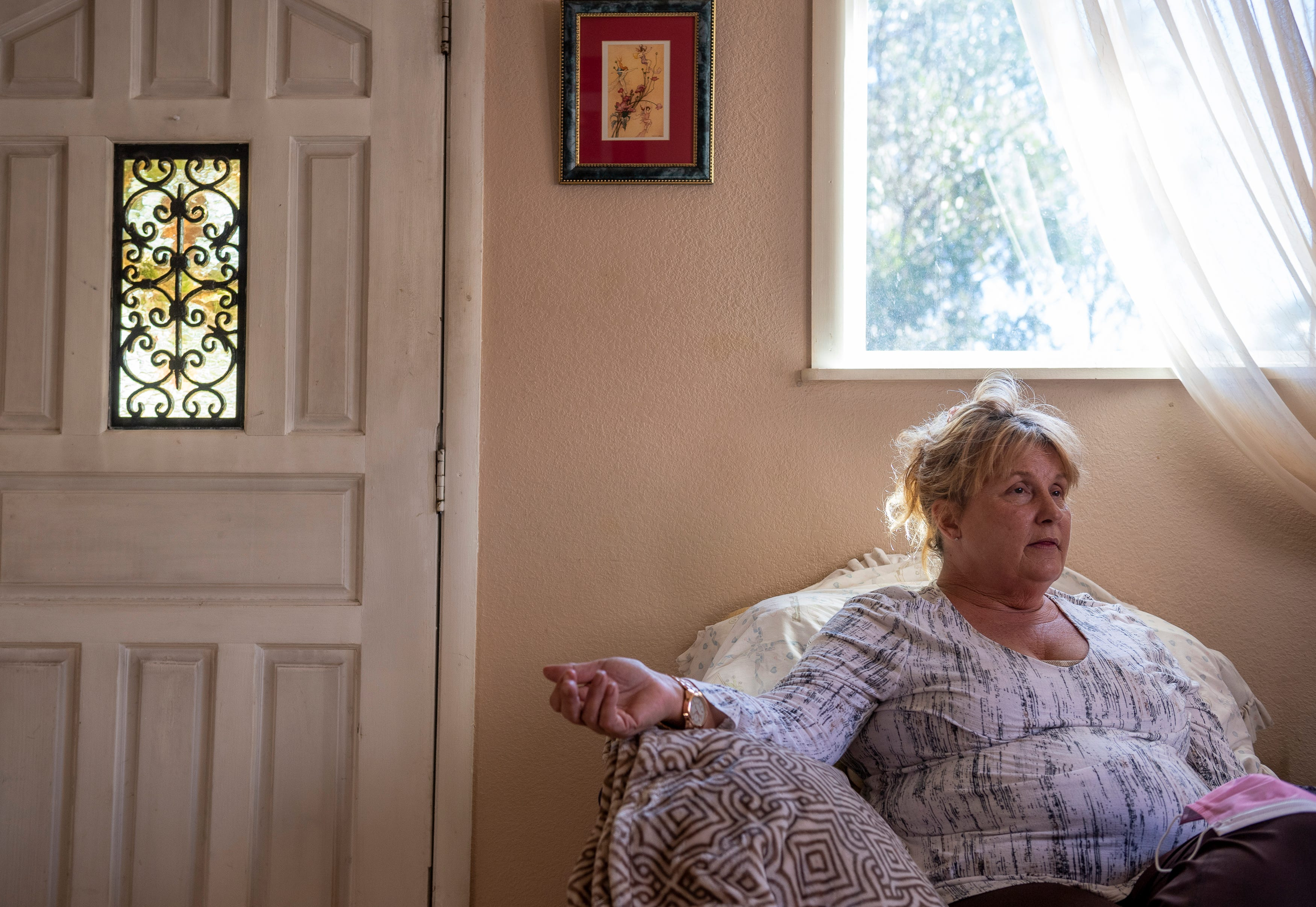 Susan Brzovich sits in the living room of the home she rents in Prunedale, Calif., on Friday, Nov. 27, 2020.