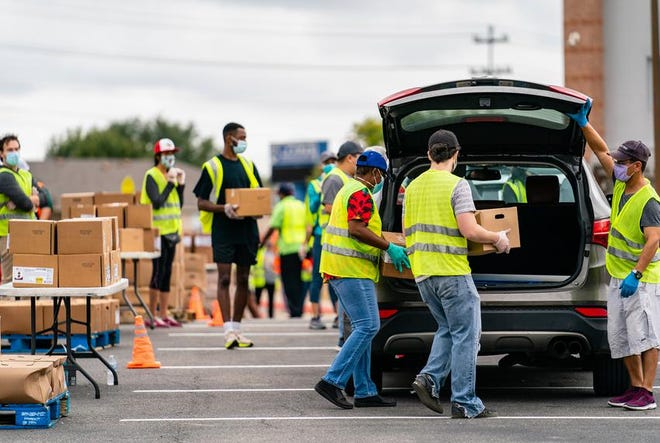 Volunteers with the Central Texas Food Bank distribute food to those in need at Lehman High School in Kyle on Nov. 14. Several organizations are providing help — and asking for assistance — as coronavirus infections increase heading into the holidays.