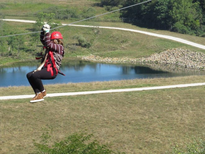 A girl takes a ride on the zipline at The Wilds during a summer excursion.