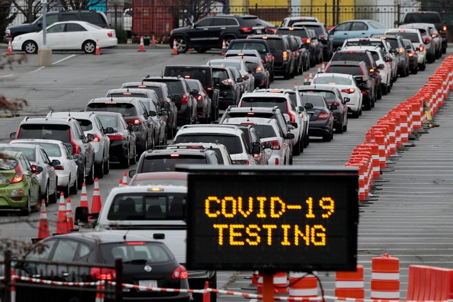 Hundreds of motorists line up at the Whale's Tooth parking lot in New Bedford, Mass., to be tested for COVID-19. (Peter Pereira/The Standard-Times via AP) ORG XMIT: MABED301