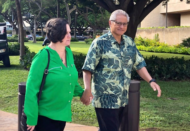 In this March 12, 2019, file photo, retired Honolulu police chief Louis Kealoha and his wife, former deputy city prosecutor Katherine Kealoha, hold hands while walking to U.S. district court in Honolulu.