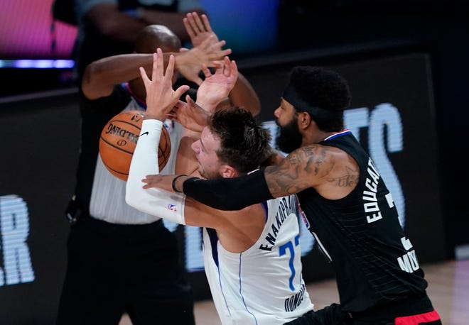 In this Aug. 30 file photo, Dallas Mavericks' Luka Doncic (77) is fouled by Los Angeles Clippers' Marcus Morris Sr. during the first half of a first-round playoff game in Lake Buena Vista, Fla. Doncic's first experience with the playoffs ended with questions about whether Morris was intentionally trying to hurt the young Dallas sensation in a first-round series won by LA.