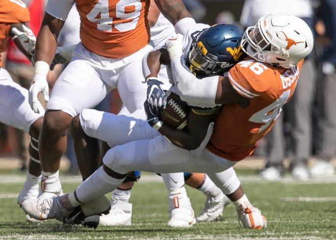 Texas linebacker Joseph Ossai tackles West Virginia running back Alec Sinkfield in the first quarter at Royal-Memorial Stadium on Saturday November 7, 2020.  [JAY JANNER/AMERICAN-STATESMAN]