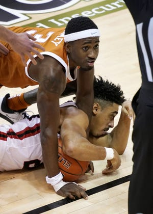 Texas guard Courtney Ramey (3) and Davidson guard Carter Collins (24) fight for a loose ball in the second half of an NCAA college basketball game in the Maui Invitational tournament, Monday, Nov. 30, 2020 in Asheville, N.C. Texas won 78-76. (AP Photo/Kathy Kmonicek)