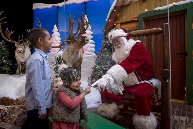 Santa visits children from behind a plexiglass divider at Bass Pro Shops this season.