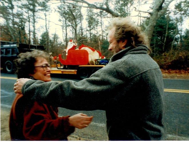 Saralee Perel and her husband, Bob Daly, share a moment on Dec. 24, 1996 as Santa and his elves deliver an 18,000-pound Christmas present to their Marstons Mills home. [Ron Schloerb/Cape Cod Times file]