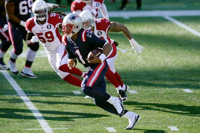 Pats quarterback Cam Newton scrambles away from Arizona Cardinals defenders Sunday in Foxboro.