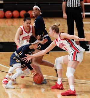 Kent State junior point guard Mariah Modkins attempts to drive past Ohio State defender Dorka Juhasz (right) as freshman teammate Lexi Jackson (23) sets a screen on Buckeyes guard Madison Greene (back left) during KSU's 2020-21 season opener on Dec. 2 in Columbus.
