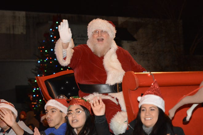 Santa waves at the crowd during the 2019 Christmas parade. This year, the parade will be in reverse, with people driving by to see floats on the side of the road.