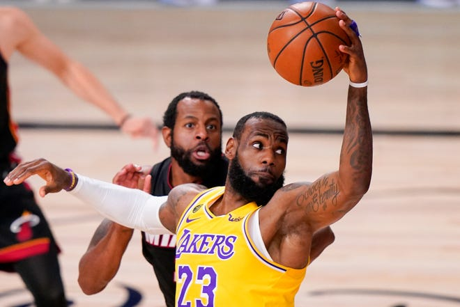 LeBron James, shown driving to the basket against the Miami Heat, has agreed to a contract extension with the Los Angeles Lakers.