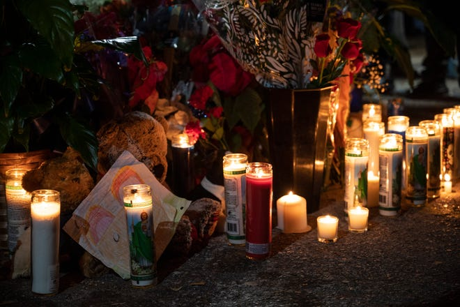 "Candles, flowers and signs line the outside of the T & N Market on Grandview St. in Mount Dora in honor of owners Mihn ""Tina"" Nguyen and ""Ken"" Khiem Ba Trinh, who were shot during an armed robbery Monday night. Tina died on scene and Ken remains in critical condition. [Cindy Peterson/Correspondent]"