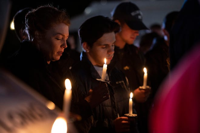 """People hold candles during a vigil in front of the T & N Market on Grandview St. in Mount Dora in honor of owners Mihn """"Tina"""" Nguyen and """"Tony"""" Khiem Ba Trinh, who were shot during an armed robbery Monday night. Tina died on scene and Ken remains in critical condition. [Cindy Peterson/Correspondent]"""