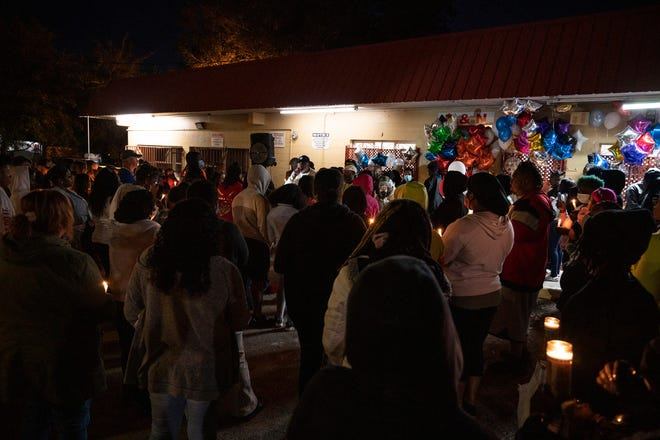 """A crowd gathers at the vigil in front of the T & N Market on Grandview St. in Mount Dora in honor of owners Mihn """"Tina"""" Nguyen and """"Ken"""" Khiem Ba Trinh, who were shot during an armed robbery Monday night. Tina died on scene and Ken remains in critical condition. [Cindy Peterson/Correspondent]"""