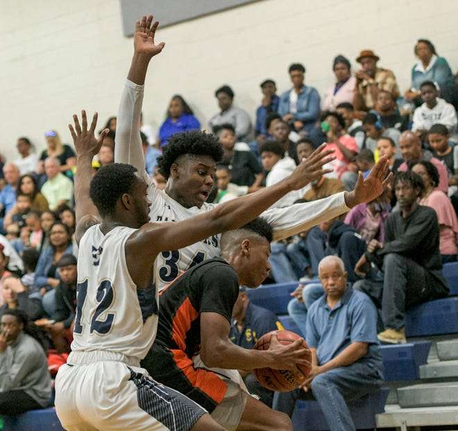 Eustis' Cory Robinson (12) and Jaden Green (34) block every move from Leesburg's Jyre McCloud (23) during a game in January between the rival schools in front of a capacity crowd at the Panther Den in Eustis. [PAUL RYAN / CORRESPONDENT]