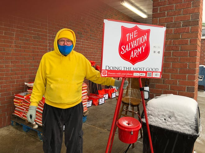 David Pierce, 88 years old, of Cambridge stands next to the Salvation Army kettle at Riesbecks in Cambridge to collect donations for the agency.  Pierce finds manning the kettle to be fulfilling and a way to give back.