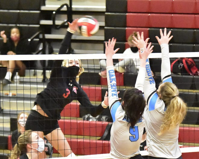 Central Davidson's Kyndall Normal is able to spike the ball over Oak Grove's Grace Manring (9) and Maya Slate (15) Tuesday night at Central Davidson.