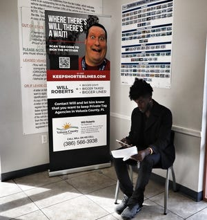 A sign shows a picture of incoming Tax Collector Will Roberts at First Daytona Tag Agency, a privately-run tag office at 927 Beville Road in South Daytona.
