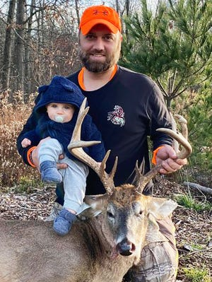 """Wayne County's own Brian Swingle ended a personal five-year drought by bagging this nine point buck. The proud Papa is pictured here with his """"biggest"""" fan, six month old son Owen."""