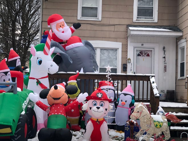 Santa, Mickey a masked Grinch and several other supporting characters greet visitors at 119 Maple St. in Hornell. The Christmas-outfitted group add holiday magic to the neighborhood.