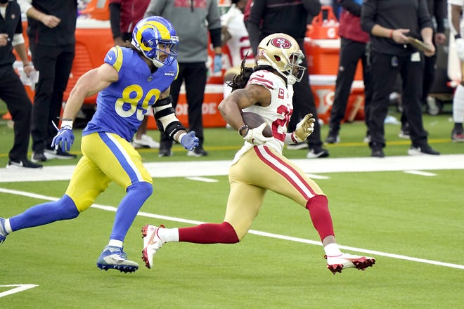 San Francisco 49ers cornerback Richard Sherman (right) runs back an intercepted pass ahead of Los Angeles Rams tight end Tyler Higbee during Sunday's game in Inglewood, California.