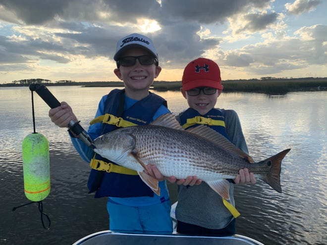 """John and James Treace with one of many reds they caught fishing in Palm Valley with Capt. Leon Dana, who said the brothers """"crushed it."""""""
