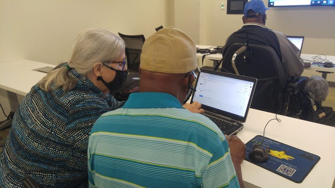 Pat Carlton of AmeriCorps goes over a lesson with a student enrolled in a free Digital Literacy workshop offered recently by the Literacy Alliance of Northeast Florida at the Jessie Ball duPont Center in downtown Jacksonville.