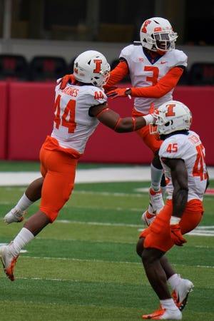Illinois defensive back Marquez Beason (3), linebacker Tarique Barnes (44) and linebacker Khalan Tolson (45) celebrate a turnover during the first half of a game against Nebraska in Lincoln, Neb. on Saturday, Nov. 21. (AP Photo/Nati Harnik)