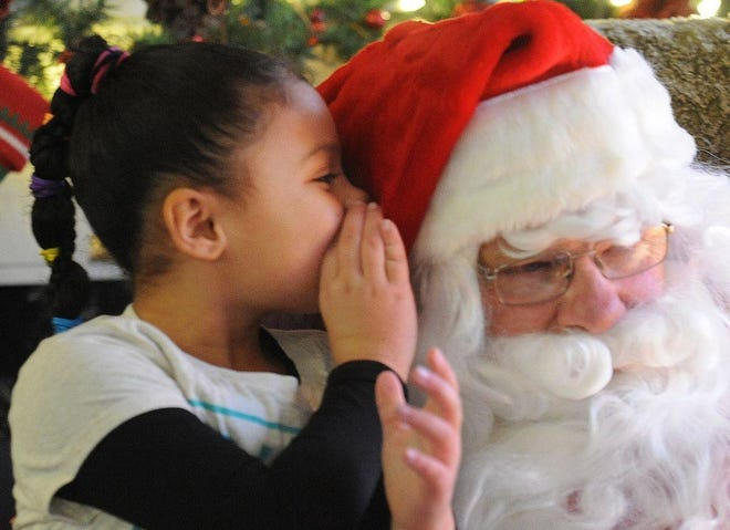 Adriana Bates, 7, whispers her Christmas wishes into the ear of Santa Claus, during Our Gift To You at The Herald News in 2014.