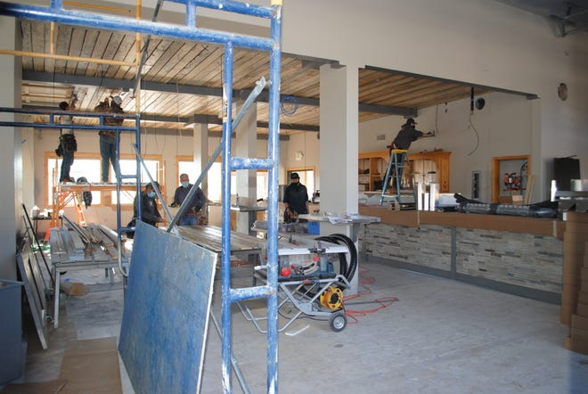 Workers put the finishing touches on a 2,000 square foot expansion of the Ski Park's bar. The project had long been a goal of former owner Ray Merlo, who passed away last summer.