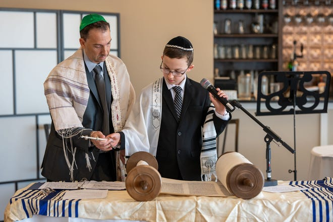 Gabriel Liftman and his father, Scott, stand over a Torah during Gabriel's bar mitzvah at Conrad's Restaurant in Walpole on Saturday, Nov. 28, 2020.    [Courtesy Photo]