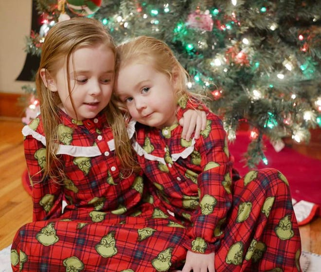 Willow, age 8, and River Roe, 6, embrace in front of their Christmas tree. Willow and River are the daughters of Amanda Black and Benjamin Roe of Pontiac.