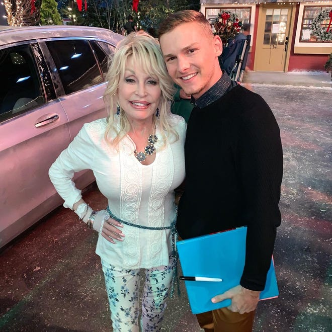 "Native Pekinite Brandon Hudson, right, with Dolly Parton. Hudson recently made his movie debut in the musical ""Dolly Parton's Christmas on the Square."""