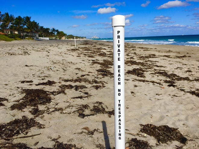 Posts in the sand at a beach in Palm Beach denote private beach ownership to the landward side of the post and public access to the ocean side.