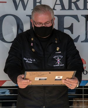 Bobby Page, owner of the Village Barber Shop, checks out the Citizens Veteran Supporter award that he was given by AmVets Pitman Post 1947 commander Michael L. Emerson during a short ceremony in front of Page's shop in Lincoln Center in Stockton. The award recognizes Page's efforts in support of veterans.