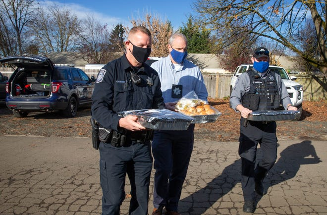 Eugene police officer David Clark, left, Detective Sean Kelley and Community Service Officer Kelsey Anderson deliver trays full of Hole in the Wall barbecue Wednesday afternoon for the people who work for St. Vincent de Paul's Lindholm Center and Dusk to Dawn site.