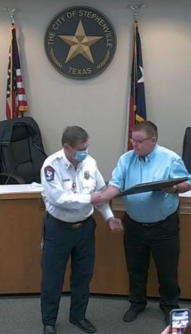 Stephenville Fire Chief Jimmy Chew, left, is presented a proclamation by Mayor Doug Svien on Tuesday honoring Chew for 50 years of service.