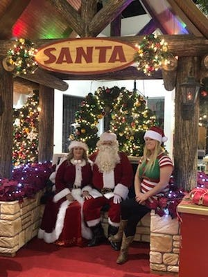 Carriers for Kids toy drive founder Jennifer Kirk, at right, sits for a photo with Mr. and Mrs. Claus.