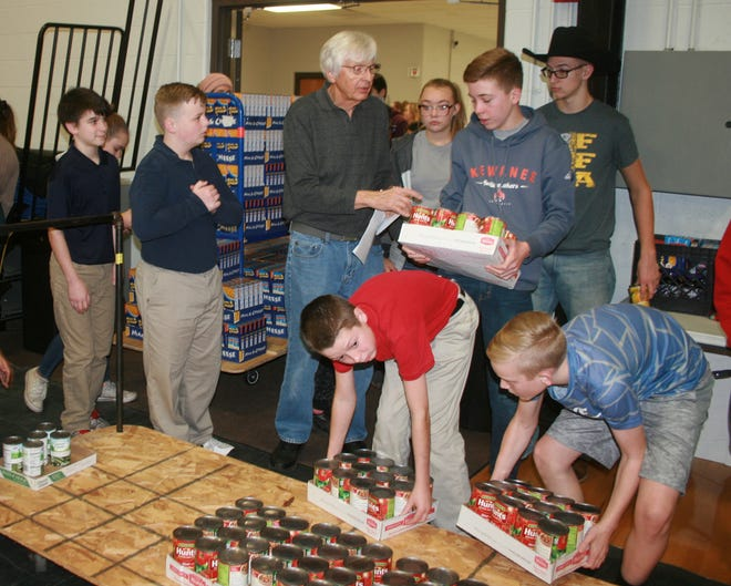 Good Fellow's vice president Ken Knowles directs student volunteers on which food items to place in which baskets during 2018's packing event in the Central School gym.