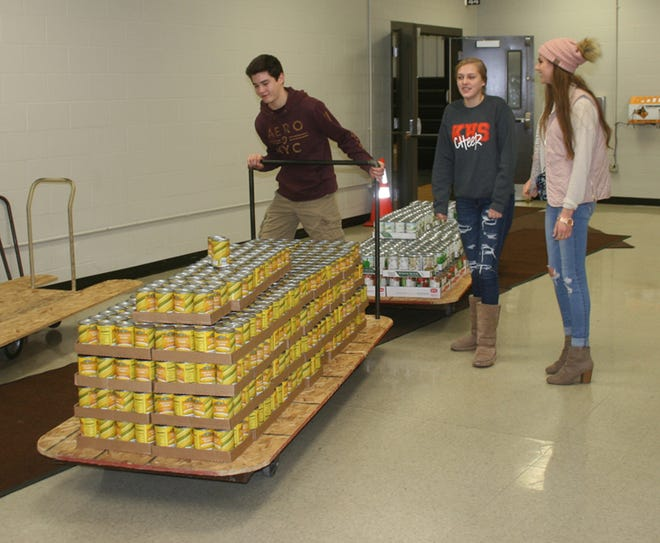 Student volunteers help fill Good Fellows Christmas baskets in 2018 inside the Central School gym.