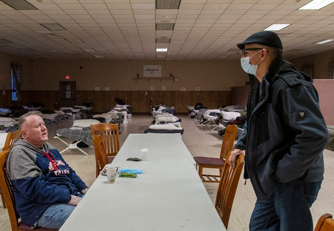 The Rev. Richie Gonzalez, right, talks to a homeless man who goes by the name C.J. in the Hotel Grace shelter Wednesday. Pastor Gonzalez is the founder and executive director of Net Of Compassion which runs the shelter at Ascension Church on Vernon Street in Worcester.