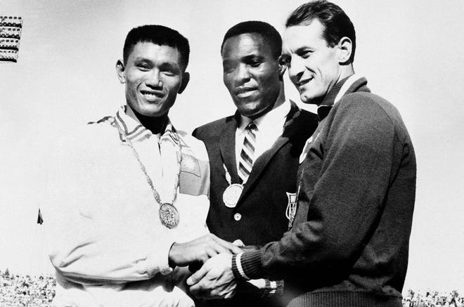 Rafer Johnson is flanked by C.K. Yang, left, and Vasily Kuznetsov after receiving their medals following the 1960 Olympic decathlon.