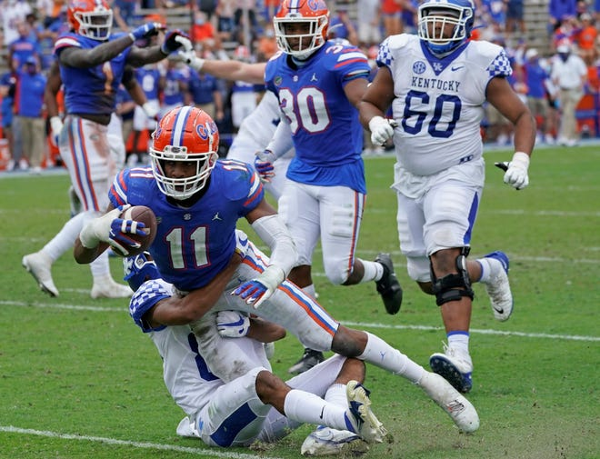 After intercepting a pass, Florida linebacker Mohamoud Diabate dives for extra yardage over Kentucky tight end Keaton Upshaw during the second half Saturday at Ben Hill Griffin Stadium.