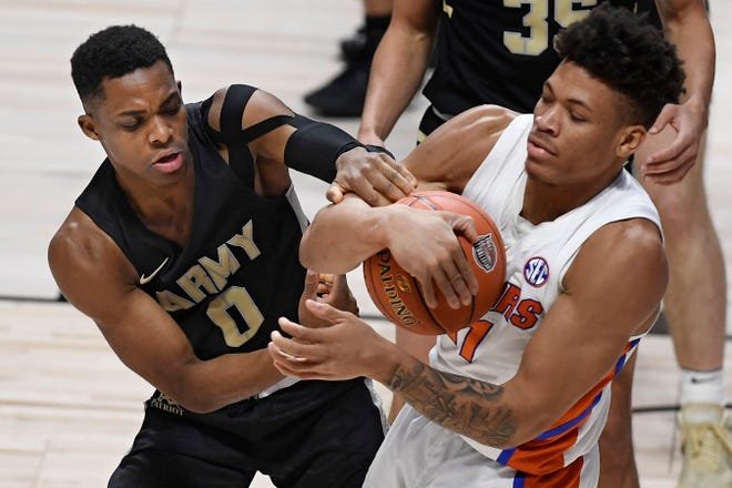 Army's Josh Caldwell, left, and Florida's Keyontae Johnson fight for possession of the ball in the second half Wednesday in Uncasville, Conn.